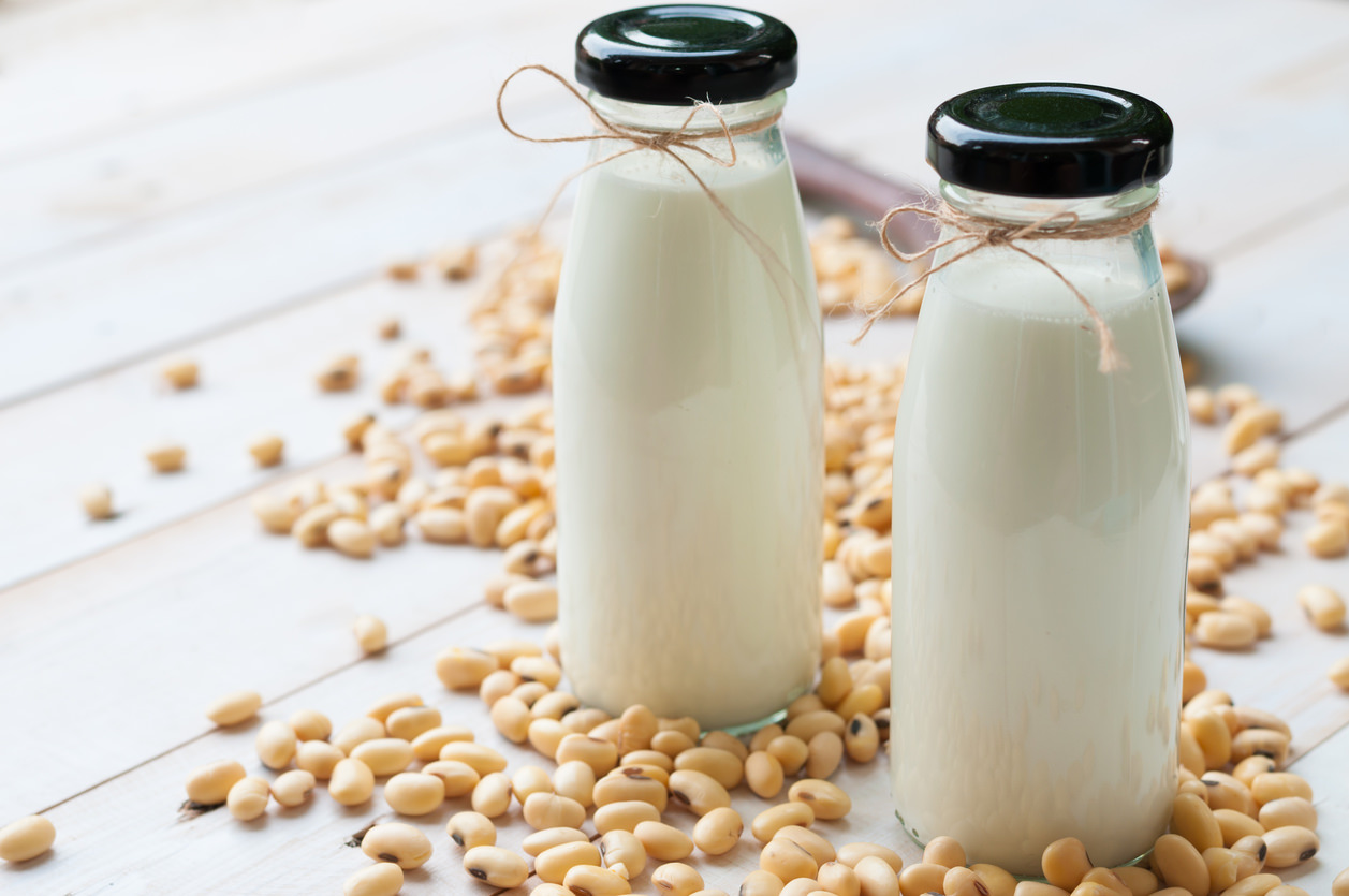 Soy milk in  glass bottle with soy pods