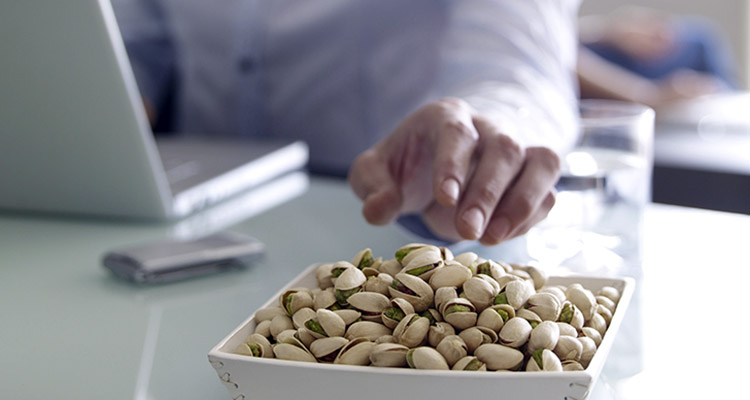 Man in office with laptop eating pistachios